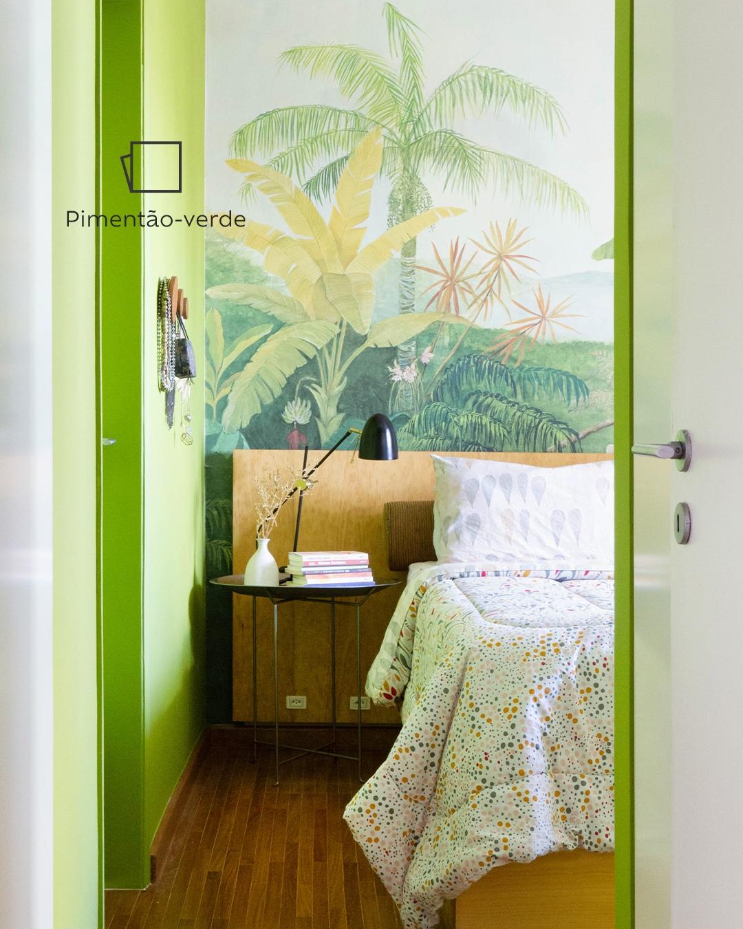Temos a foto da parte superior da cama de Joana vista pelo lado direito, focando na parede ao lado da cama com a cor Pimentão-verde e um ícone de cor.