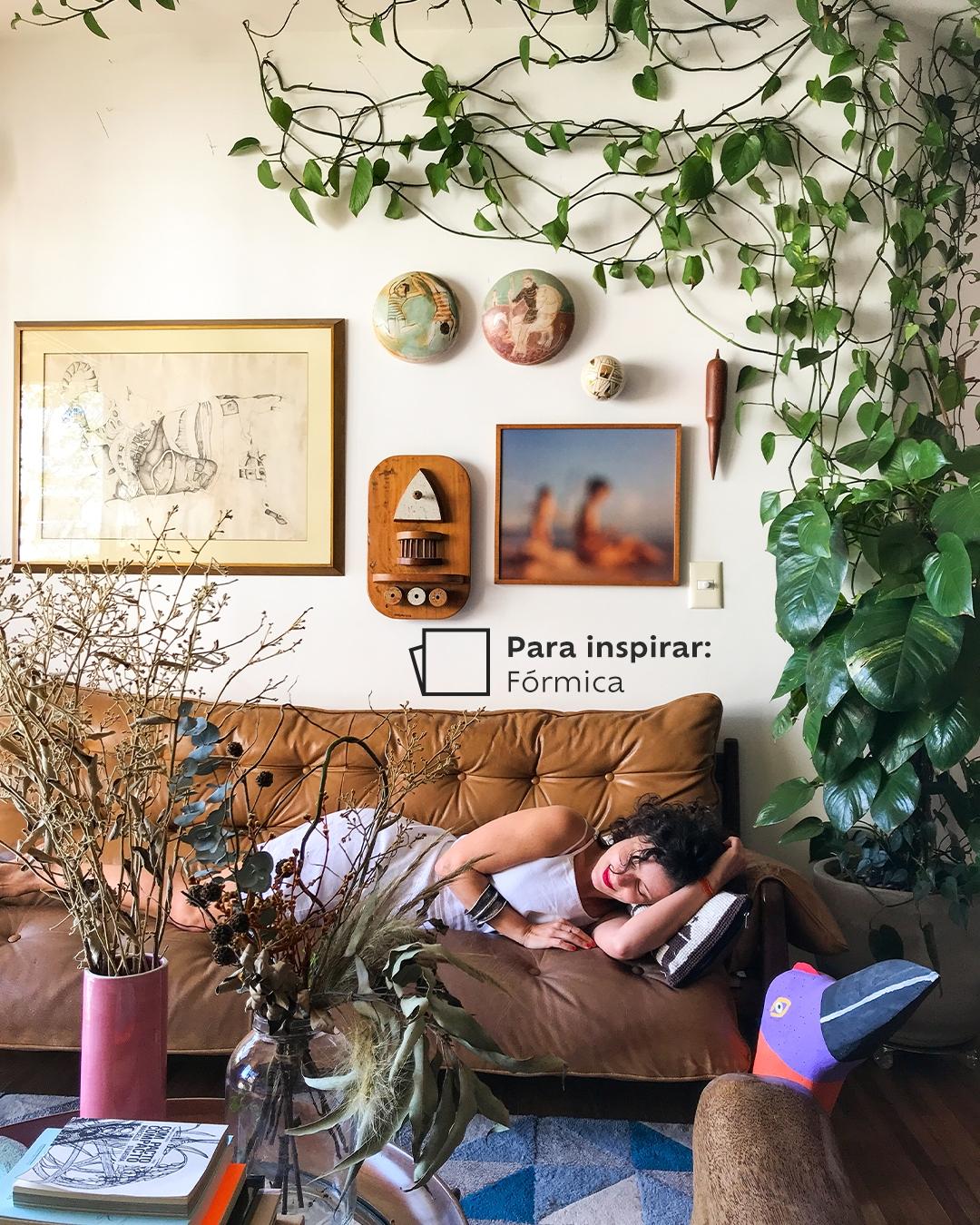 Na foto, temos Joana Lira deitada em seu sofá com plantas ao redor, e quadros pendurados na parede atrás dele. Para inspirar, temos a cor Fórmica na parede e um ícone de cor.