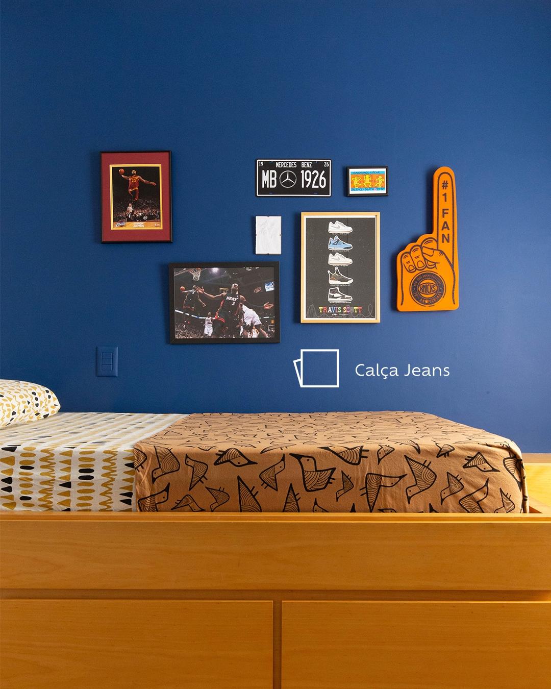 Foto do quarto de Joaquim com a parede de quadros vista de frente. Vemos outros quadros da temática de basquetebol, a cor Calça Jeans pintada na parede e um ícone de cor logo abaixo.
