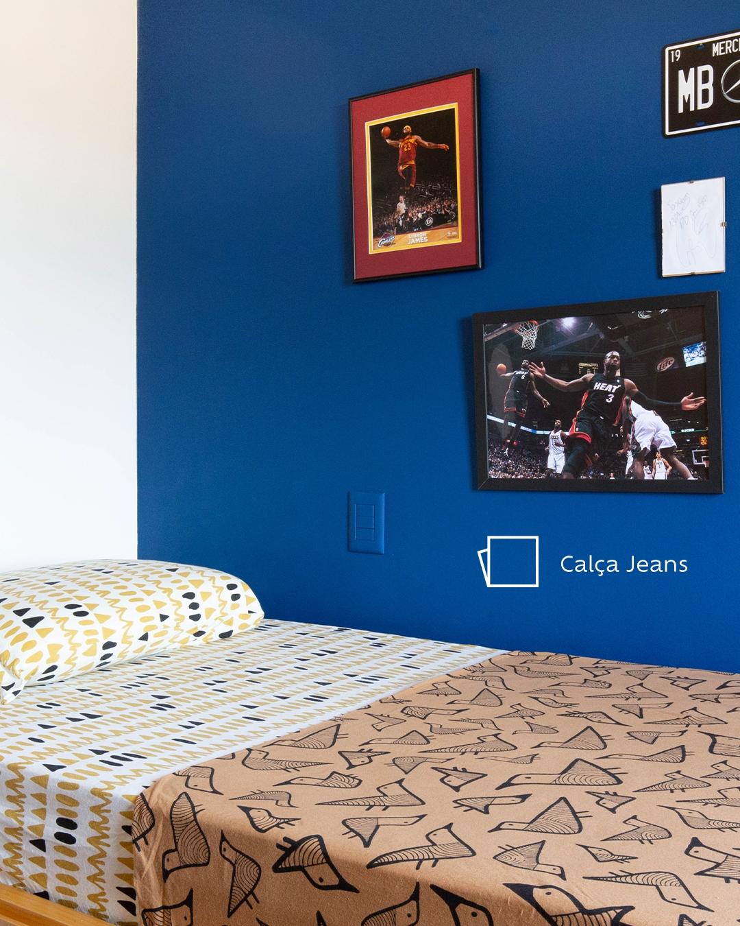 Foto do quarto de Joaquim com foco na sua cama vista verticalmente e na parede pintada da cor Calça Jeans com um ícone de cor. Na parede, vemos quadro de jogadores de basquete e o ícone da cor. A cama tem um lençol com desenhos de pássaros e outro com desenhos triangulares
