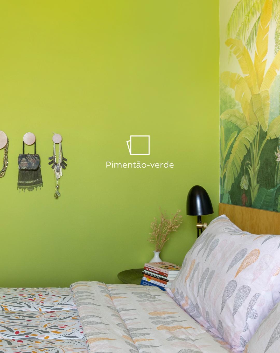 Na foto temos o lado esquerdo da cama de Joana vista de frente, com sua mesinha de cabeceira com livros e uma luminária. Ao fundo, um papel de parede com palmeiras e ao lado esquerdo, a parede pintada na cor Pimentão-verde com um ícone de cor.