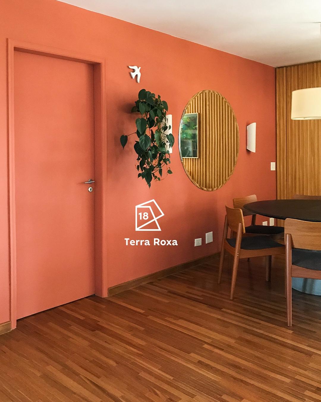 Na foto, vista da sala de Joana Lira com a parede ao fundo pintada de Terra Roxa e seu ícone de cor do ano 2018, um espelho pendurado e uma planta. Ao lado esquerdo, temos uma porta também pintada na cor. Ao lado direito, uma mesa redonda e duas cadeiras.