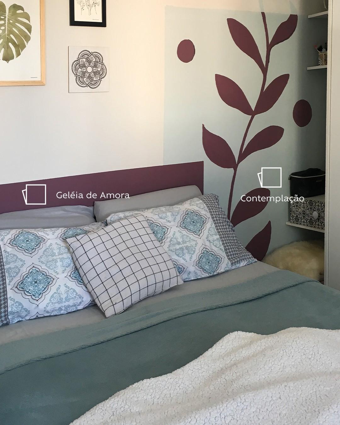 Foto de quarto com foco na cabeceira da cama, aparecendo alguns travesseiros com fronhas azul e cinza. Ao fundo, a parede pintada na cor Contemplação, uma pintura geométrica quadrada que simula a cabeceira da cama na cor Geleia de Amora e um desenho de planta na mesma cor ao lado direito da cabeceira.