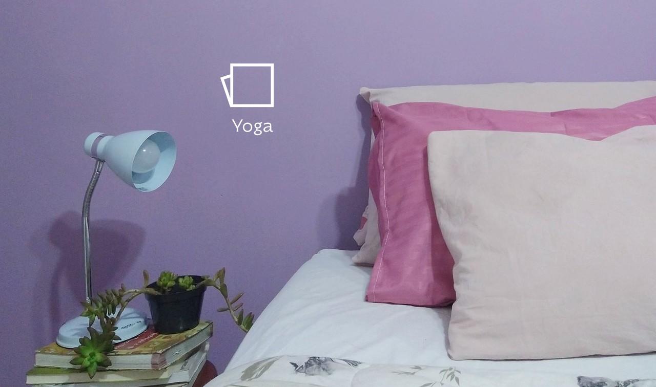 Foto do quarto com foco ao lado esquerdo da cama, mostrando três travesseiros em diferentes tons de rosa. Ao lado esquerdo, alguns livros em cima de uma mesa de cabeceira, e uma luminária e um vasinho de planta em cima deles. Ao fundo, a parede pintada na cor Yoga e o ícone de cor.