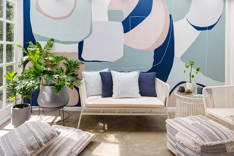 Foto de área externa com um banco com almofadas brancas e um vaso de plantas cinza centralizados. A frente, algumas almofadas maiores. Ao fundo, a parede pintada com formas orgânicas nas cores Chão Batido, Azul-marinho e Mantra.