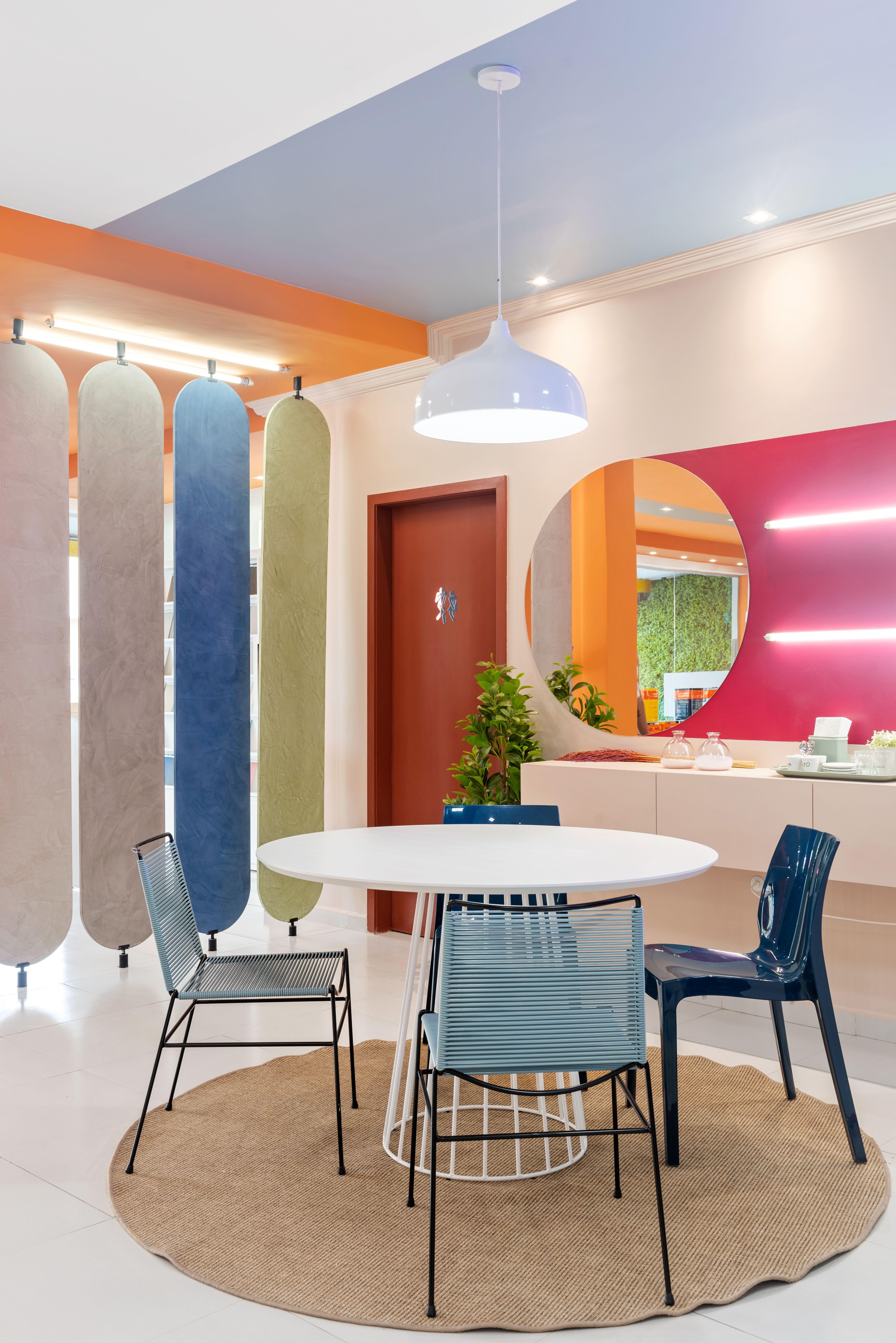 Foto de ambiente na loja Monza Tintas com uma mesa branca em primeiro plano com cadeiras azul. Ao fundo, parede do lado direito com um espelho e uma faixa em um tom de rosa intenso e luzes. Ao lado esquerdo, uma porta e alguns painéis de madeira em cores diversas