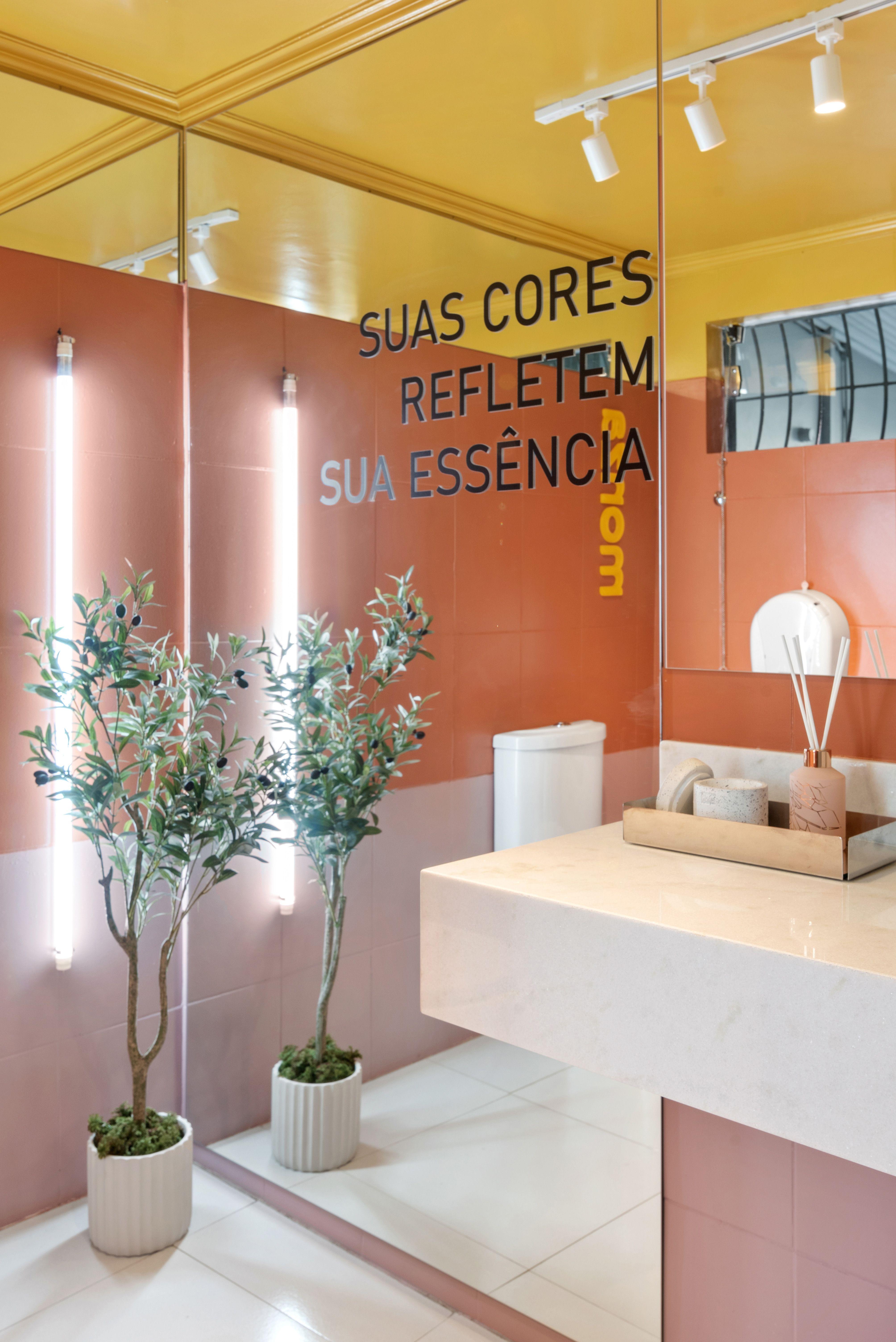 """Foto de banheiro na loja Monza Tintas com um grande espelho em foco com as escritas """"Suas cores refletem sua essência"""". Do lado direito inferior, um vaso com uma árvore média. Do lado direito, uma pia de banheiro com difusor de ambiente."""