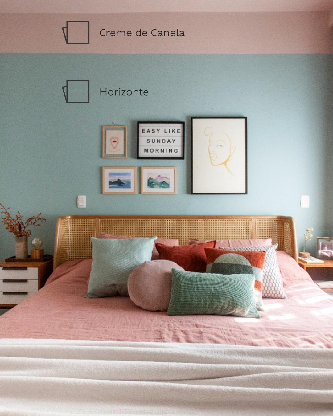 Foto do quarto de frente para a cama centralizada, que possui uma colcha rosa e almofadas rosa e verde. Ao fundo, a cabeceira de palha e cinco quadros de tamanhos diferentes pendurados na parede, pintada com a cor Horizonte e a faixa na cor Creme de Canela acima.