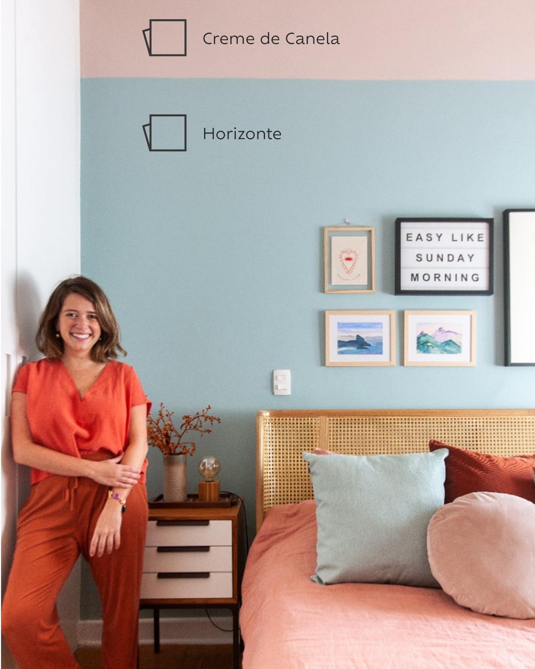 Foto do quarto na mesma perspectiva da foto anterior, com foco no lado esquerdo da cama, com a Duda Senna de macacão laranja apoiada na parede ao lado da cama.
