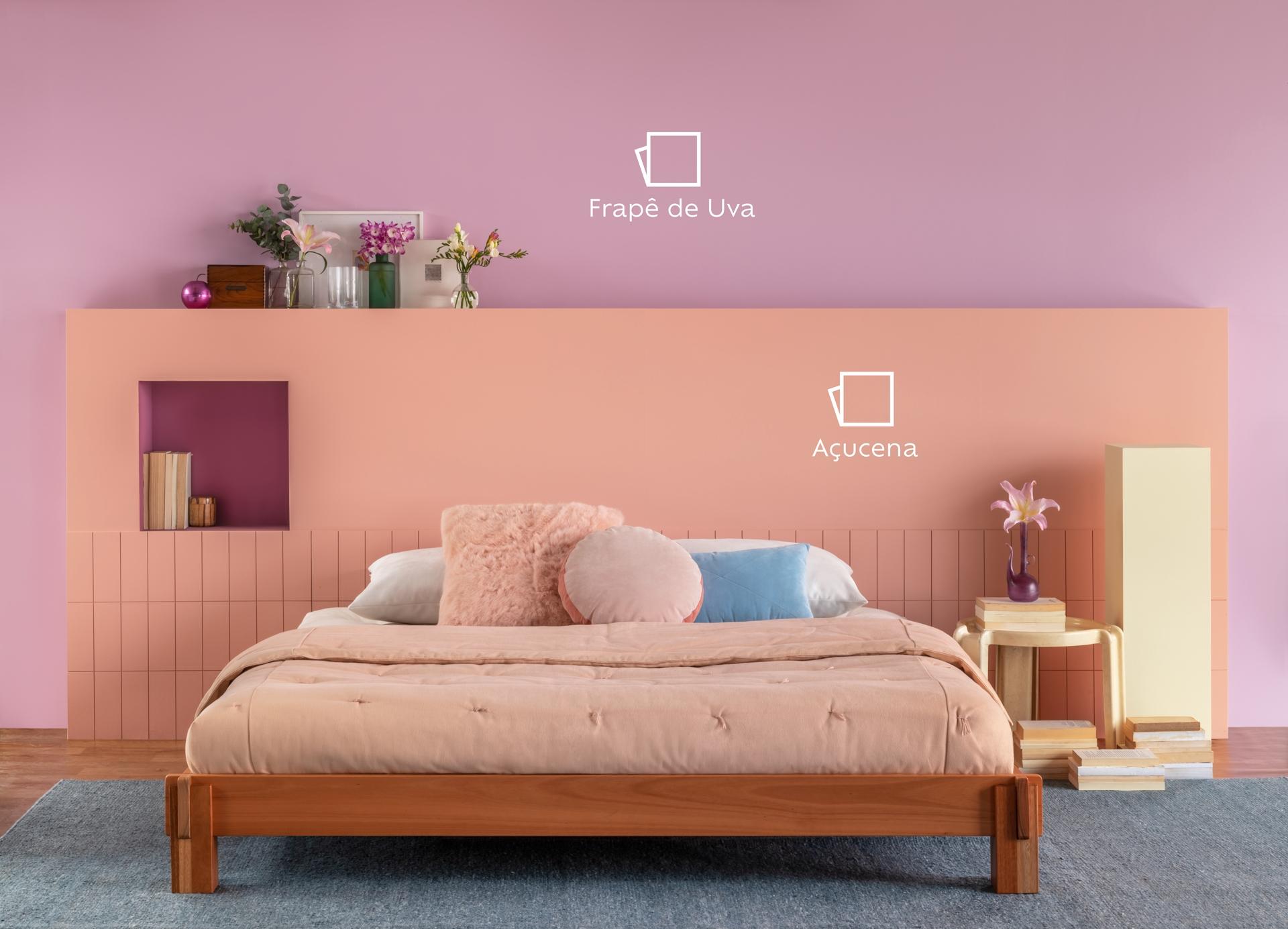 Foto de um ambiente com uma cama em primeiro plano. Na cama podemos ver uma manta na cor rosa e algumas almofadas rosa e azul. Ao fundo, temos um quadrado pintado na parede na cor Açucena e acima, Frapê de Uva, e os ícones de cor. Ao redor da cama e em cima da pintura da cor Açucena, temos mobiliários de decoração como vasos de flores.