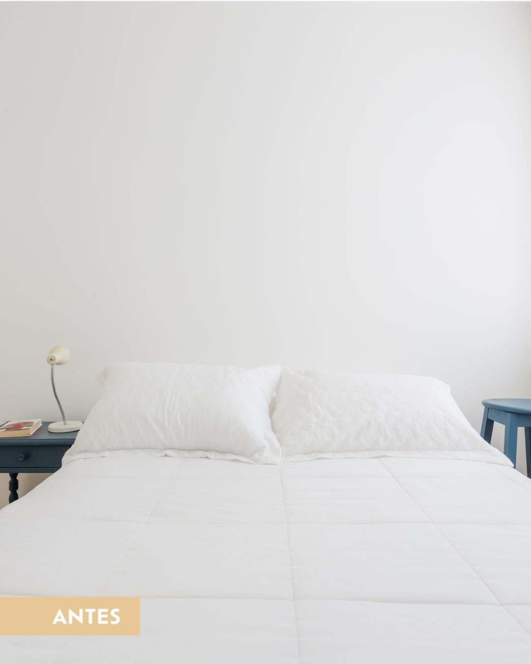 Foto do ambiente agora com uma cama e lençol brancos e almofadas com desenhos triangulares amarelos. Ao fundo, um círculo amarelo pintado na cor Nimbus simulando uma cabeceira, com prateleira e quadros pendurados.