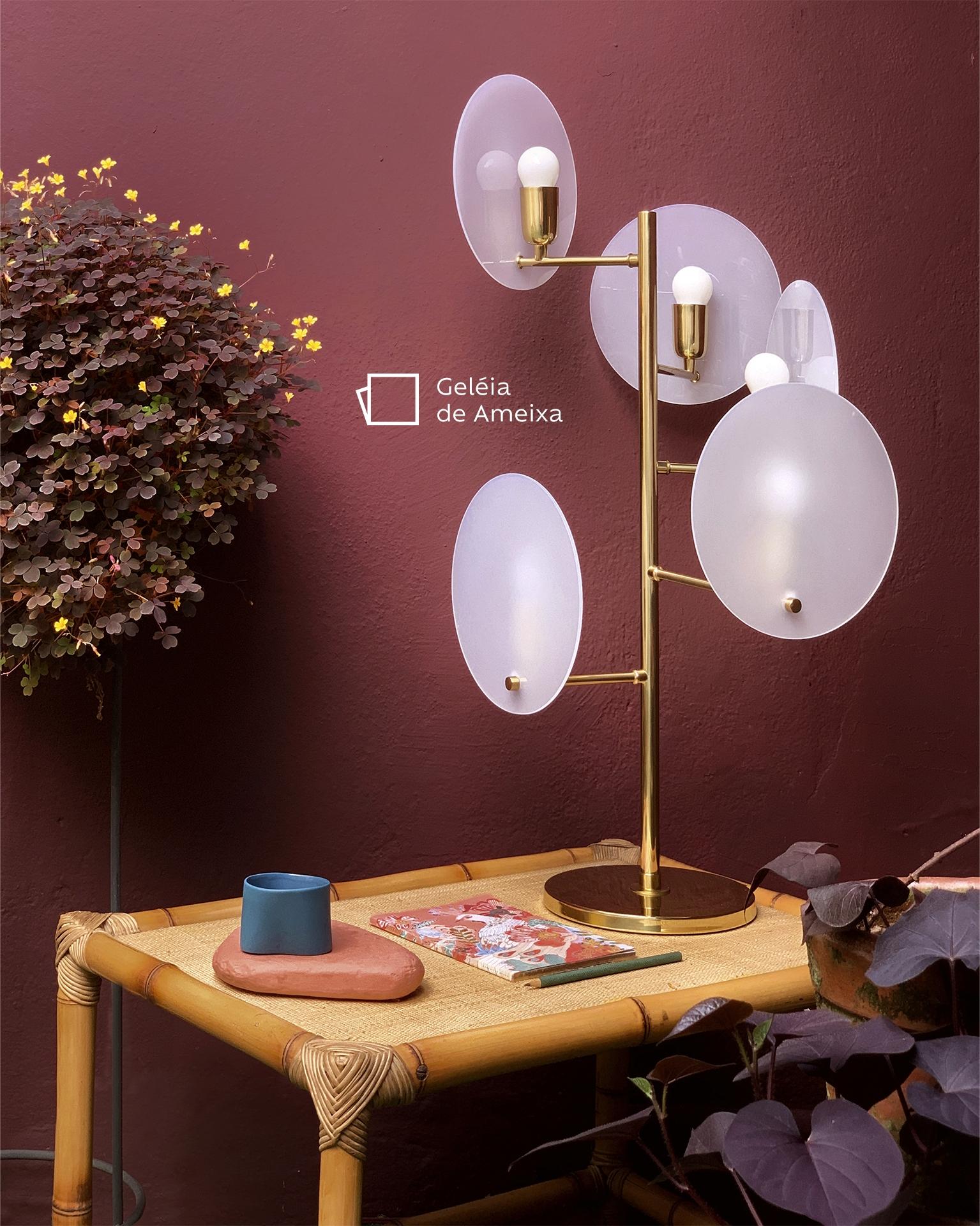 Na foto, vemos uma luminária, em cima de uma mesa de bambu, com quatro círculos ligados à uma base central. Na mesa, há um caderno com a capa florida e um lápis, e alguns itens de decoração. Ao fundo, uma árvore com folhas roxas e amarelas e a parede pintada na cor Geleia de Amora, com o ícone de cor.