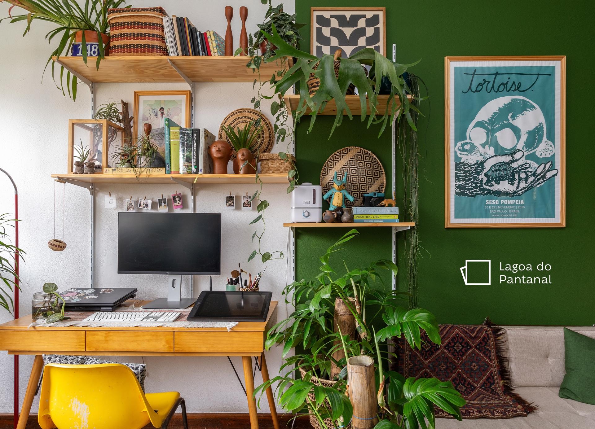 Foto tirada de frente para uma parede com prateleiras com plantas e mobiliário de decoração, e ao lado esquerdo, uma mesa com um computador e uma cadeira amarela abaixo. Ao lado direito, um quadro pendurado na parede fazendo uma brincadeira com uma tartaruga e um crânio e, abaixo, um sofá com manta e almofada. Ao fundo, a parede está dividida ao meio verticalmente, ao lado esquerdo a cor é Branca e ao lado direito, temos a cor Plantação de Hortaliças, com o ícone de cor entre o quadro e o sofá.