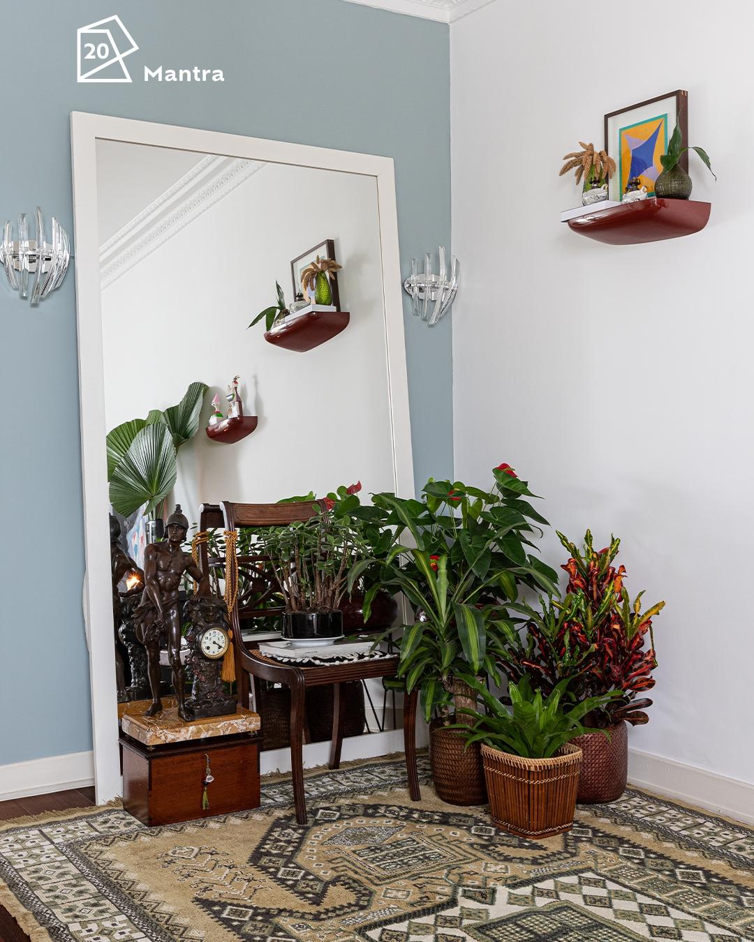 Foto da sala com um espelho grande em destaque e alguns vasos de planta na frente. Ao fundo, a parede pintada na cor Mantra e o ícone de cor do ano 2020 acima do espelho.