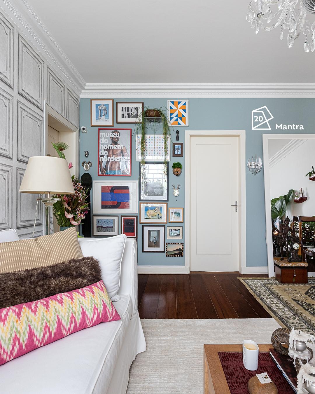 Foto da sala de Fabiano com um sofá com almofadas de diversas estampas na parte esquerda inferior da foto e, ao fundo, diversos quadros na parede que está pintada na cor Mantra. Ao meio, temos uma porta ainda branca com o ícone de cor do ano 2020 da cor Mantra.