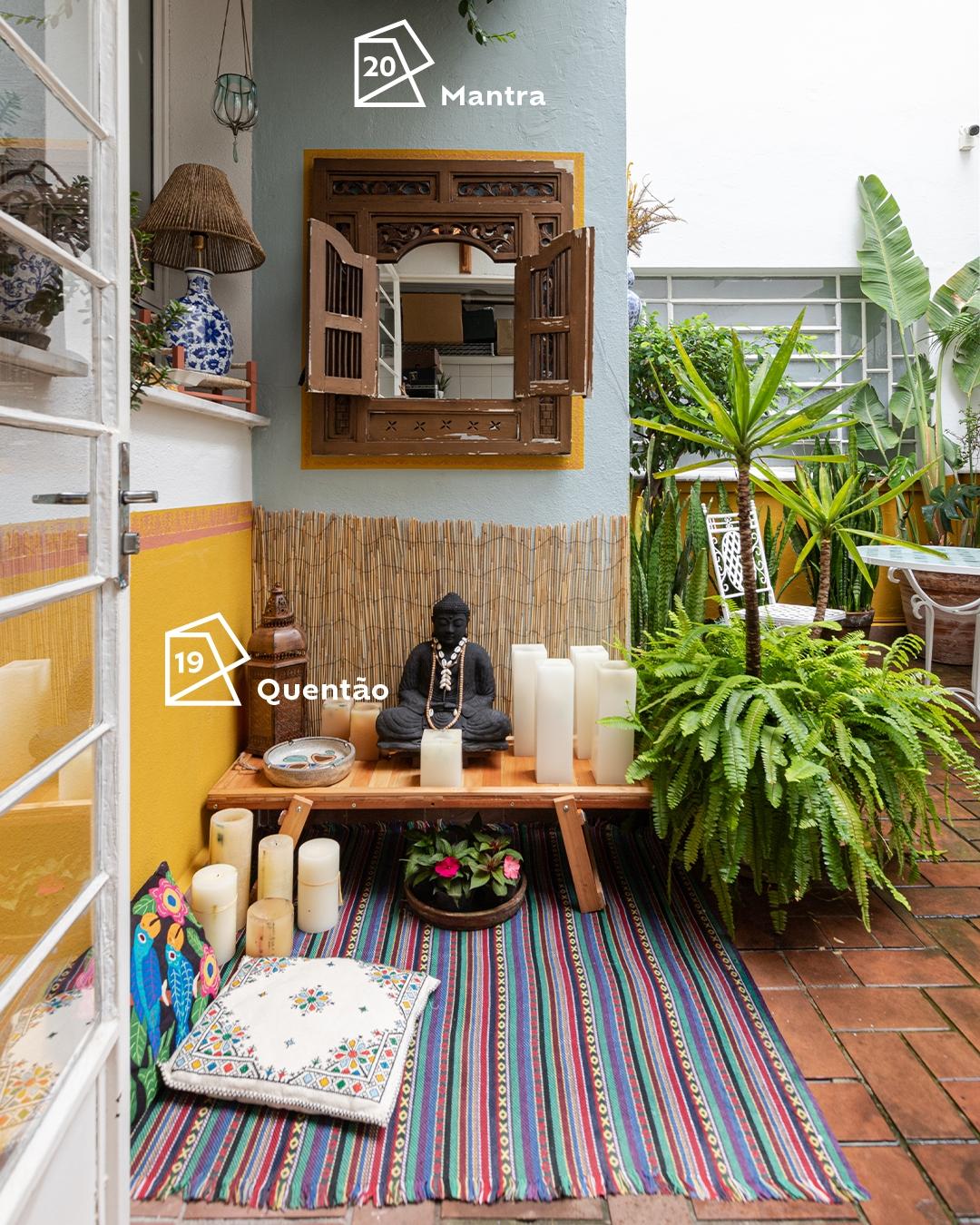 Foto de área externa com um canto em foco. Vemos uma figura religiosa (Buddha) em cima de uma mesa com velas ao redor, um tapete e as paredes pintadas nas cores Quentão e Mantra, e seus ícones de cor do ano 2019 e 2020 respectivamente.