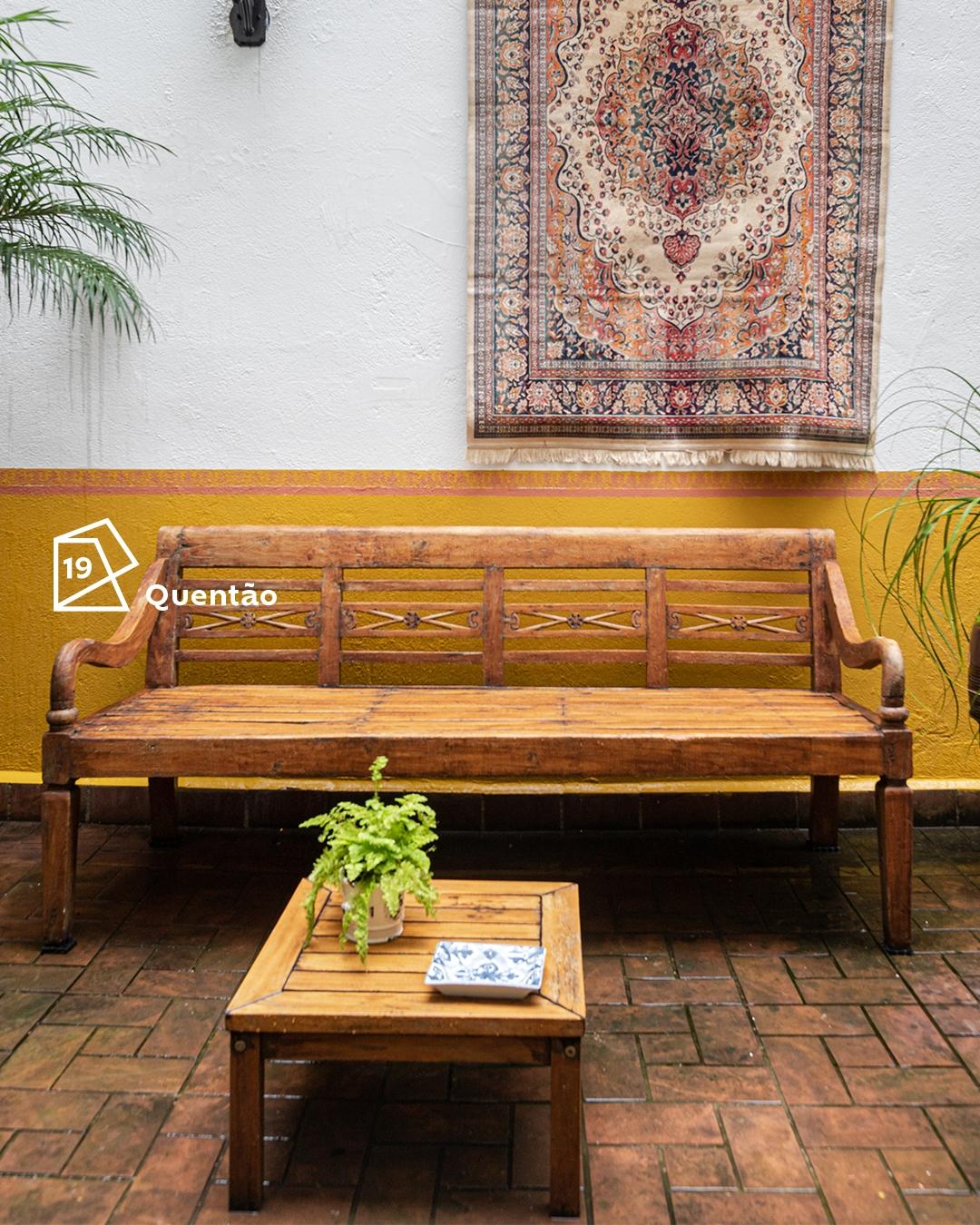 Foto de área externa com um longo banco de madeira ao centro e uma mesa de centro um pouco à frente. Ao fundo, a parede com a técnica de meia-parede horizontal na cor Quentão na parte de baixo, e o ícone de cor do ano 2019. Acima, um tapete pendurado como item de decoração.