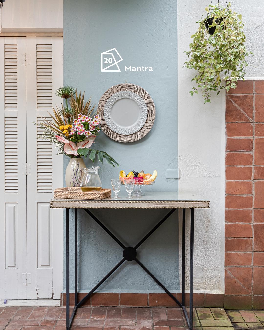 Foto de área externa com uma mesa ao centro com itens de decoração em cima. Ao fundo, uma faixa vertical pintada na parede com a cor Mantra e o ícone de cor. Ao lado direito, uma planta pendurada.