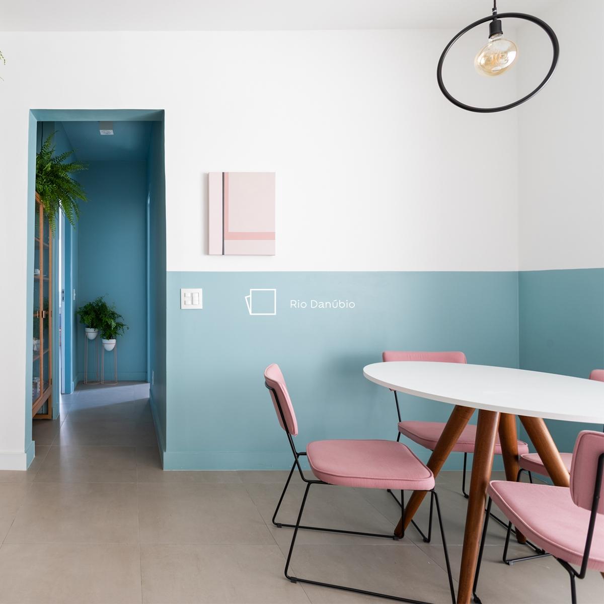 Foto de ambiente com uma porta aberta ao lado esquerdo, do lado direito a parede está pintada com a técnica meia-parede na cor branca na parte de cima e com a cor Rio Danúbio na parte de baixo, e o ícone de cor. Temos ainda ao lado direito uma mesa redonda branca e três cadeiras rosa.