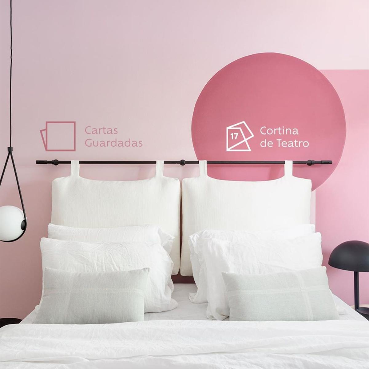 Foto de frente para uma cama com lençóis e travesseiros brancos. Ao fundo, uma parede pintada na cor Cartas Guardadas com o ícone de cor. Acima do lado direito da cama, um círculo pintado com a cor Cortina de Teatro e seu ícone de cor do ano 2017.