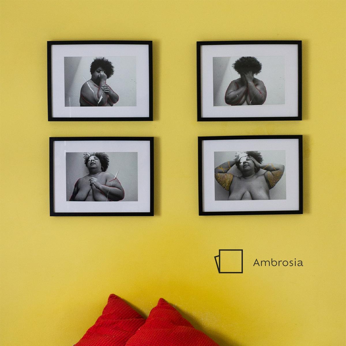 Foto de uma parede com o fundo na cor Ambrosia, e seu ícone de cor localizado do lado direito inferior. Abaixo, algumas almofadas vermelhas centralizadas. Na parede, vemos quatro quadros de uma mulher com alguns detalhes em dourado.