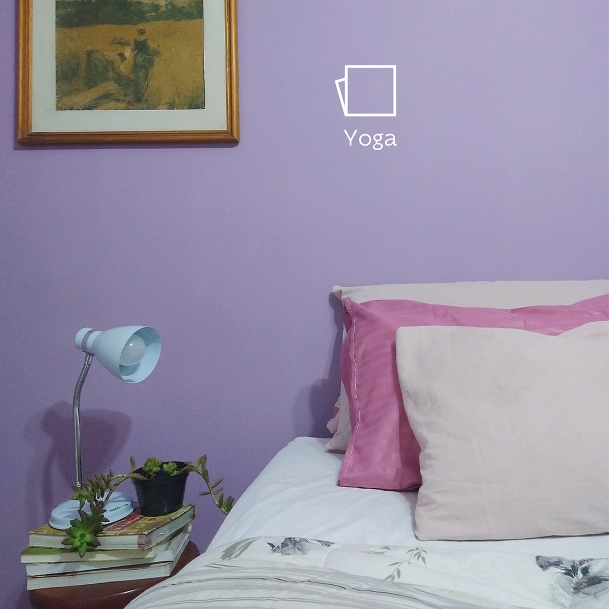 Foto do lado esquerdo de uma cama com travesseiros em diferentes tons de rosa e uma mesinha de cabeceira com livros, um vasinho de planta e uma luminária. A parede está pintada na cor Yoga com o ícone de cor.