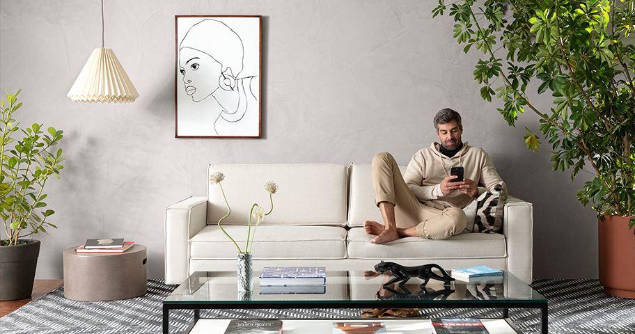 Homem relaxado sentado em sua sala onde uma das paredes apresenta o efeito cimento queimado da Suvinil