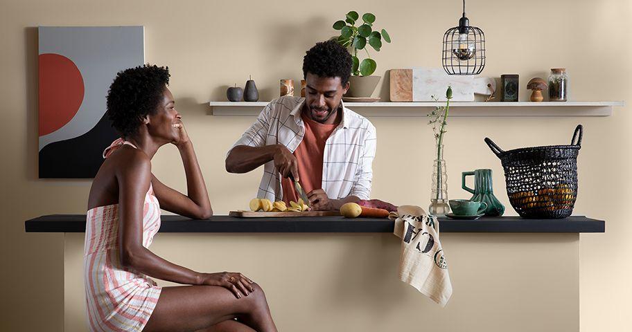 Casal cozinhando em bancada de cozinha com decoração bege.