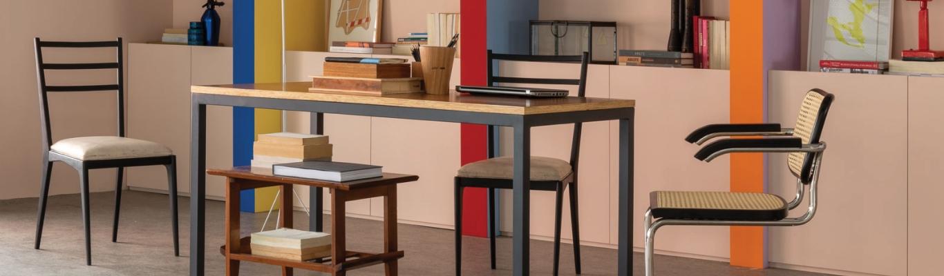 Sala colorida com diversos itens de escritório, como livros e um notebook sobre a mesa que possui cadeiras em volta