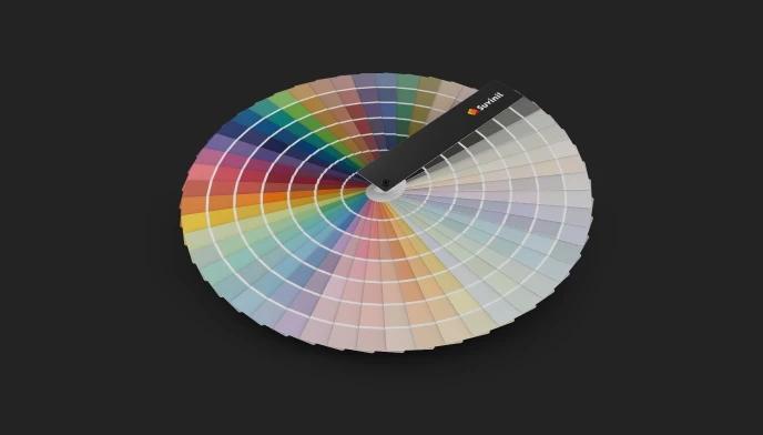 Em um fundo preto, o leque de cores da Suvinil está inteiramente aberto, formando um círculo, e mostrando suas cores e famílias, que começam nos cinzas neutros e passam por todas as nuances de luminosidade e o círculo cromático.