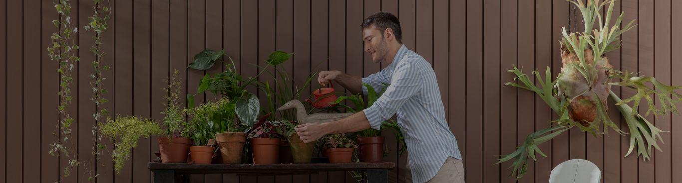 Homem regando plantas simbolizando a preocupação ambiental da Suvinil e o seu compromisso com a sustentabilidade.