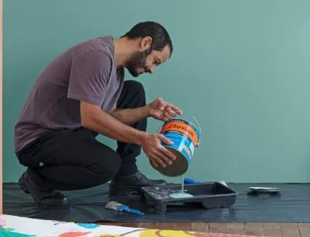 Homem preparando tinta para pintar parede de quarto.