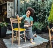 Mulher pintando superfície de madeira com tinta Suvinil.