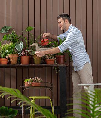Homem cuidando de plantas em área externa de sua casa, simbolizando o compromisso da Suvinil com a sustentabilidade.