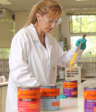 Mulher conferindo a consistência e cor da tinta Suvinil Fosco Completo.