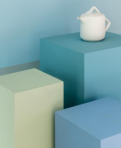 Um bule branco, de design moderno, está posicionado em cima de um de três pilares, cada qual em um tom diferente de azul, representando a versatilidade desta matiz.