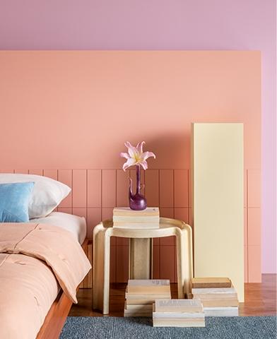 Quarto tem cama arrumada, uma mesa de cabeceira apoiando um vaso e sua flor e, ao fundo paredes pintadas em tons calmos de violetas e rosas.