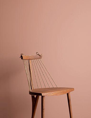 Cadeira posicionada a frente de parede pintada com a cor Flor de Anis da Suvinil.