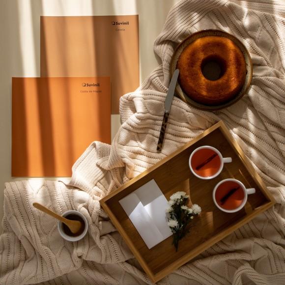 Dois Adesivos Teste Sua Cor Suvinil nos tons alaranjados Calda de Maple e Canela em uma cena que remete a um aconchegante café da manhã com bolo e uma bebida quente.